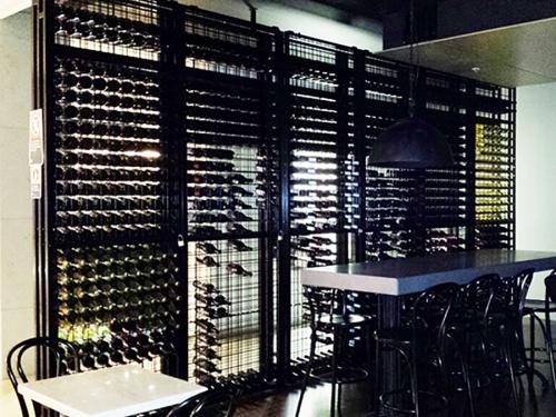 Powder Coated Lockable Connoisseur Wine Racks form a wall in a Cafe