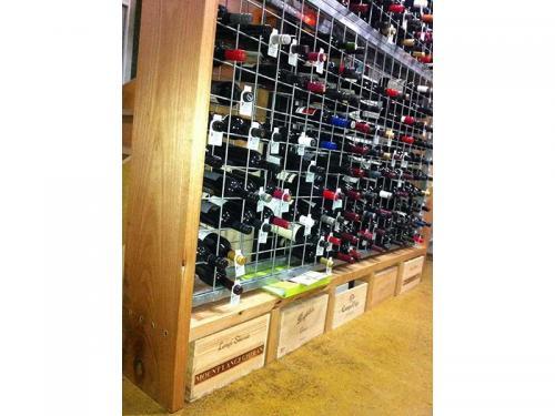 Galvanised wine racks in joinery with storage below